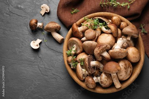 Fotografia Different fresh wild mushrooms in bowl on black background, flat lay