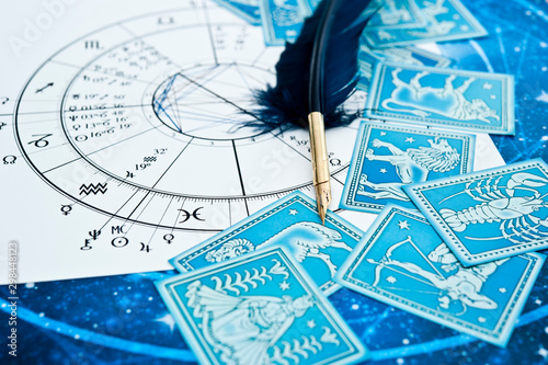 Leinwand Poster quill pen in form ob blue feather lying on horoscope and zodiac signs like astro