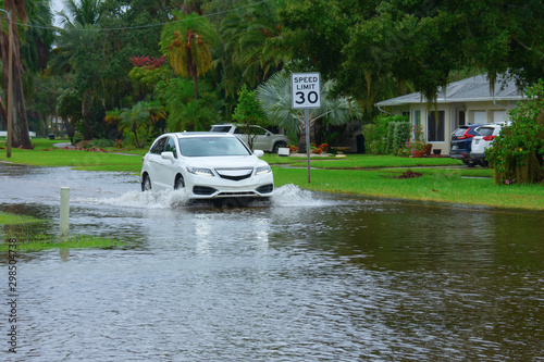 Photo Heavy flooding and storm surge in residential neighborhood with a car driving through deep splashing water in the flooded street in front of houses with Speed Limit sign on side of the road