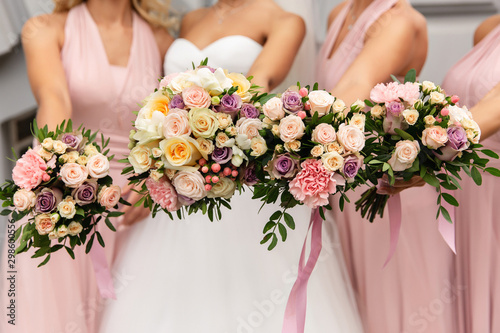 Valokuva Bride and bridesmaids in pink dresses posing with bouquets at wedding day