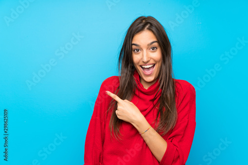 Carta da parati Young woman with red sweater over isolated blue background pointing finger to th
