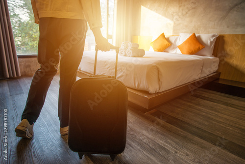 Tourist woman pulling her luggage to her hotel bedroom after check-in.