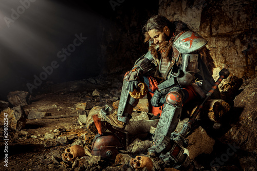 Fotografie, Obraz Powerful knight in the armor with the hammer is sitting on the stone