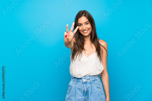 Obraz na płótnie Young woman over isolated blue background happy and counting three with fingers