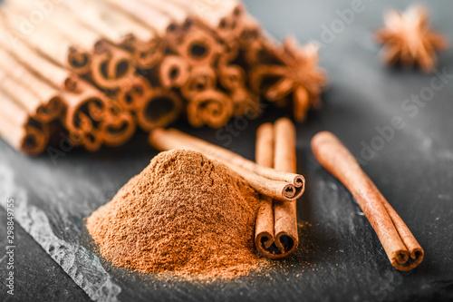 Foto Cinnamon sticks spices on dark stone table
