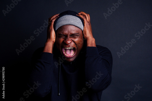 Foto worried african american face man wearing gray hat and black hoody with hood ,shouting loud and plugging covering ears i don't want to listen