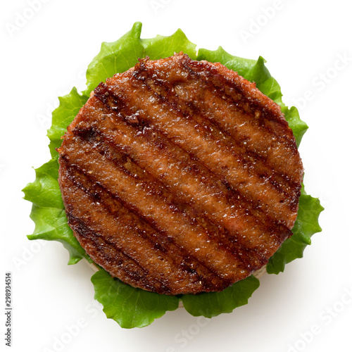 Fotografiet Freshly grilled plant based burger patty on bun with lettuce isolated on white