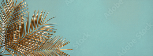 Obraz na płótnie Three gold painted date palm leaves on desaturated turquoise background