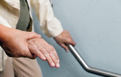 Canvastavla Elderly woman holding on handrail with caregiver