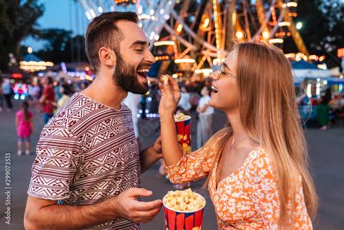 Tablou Canvas Positive loving couple in amusement park eat popcorn.