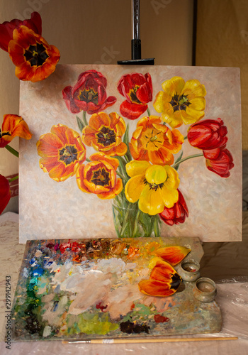 Foto The painting with tulips is on the easel with the artist's palette on the table and real flowers and petals