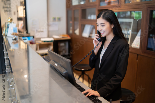 Valokuvatapetti Welcome to the hotel,Happy young Asian woman hotel receptionist worker smiling s