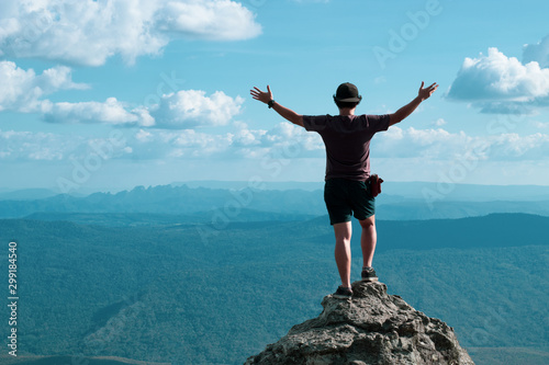 man standing on nature cliff with forest lanscape background, adventure trip tourism, holiday vacation with backpack travel to moutain