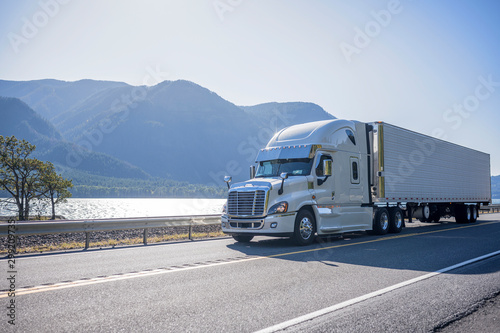 Big rig semi truck with chrome accessories transporting frozen cargo in refrigerated semi trailer moving on the road along river with bewitching view on the opposite bank
