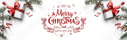 Merry Christmas text on white background with gift boxes, ribbons, red decoration, fir branches, bokeh, sparkles and confetti. Xmas and New Year greeting card, bokeh, light. Flat lay, top view