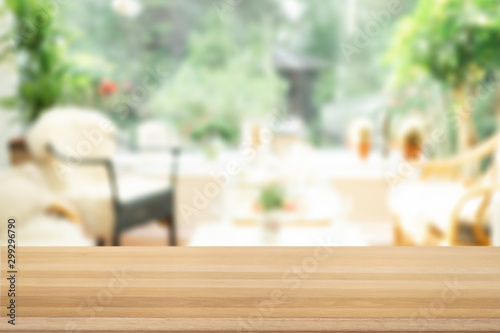 Carta da parati Brown empty wooden table top with blurred living room that can see garden background