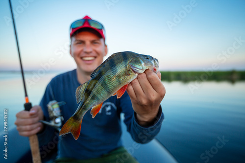 Happy amateur angler holds perch fish (Perca fluviatilis) in one hand and fishing rod in the other. Fisherman showing the fish and smiles being on the lake