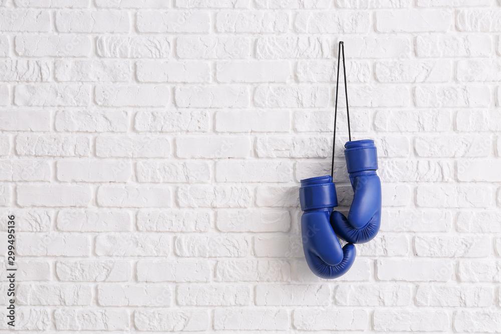 Para bokserskich rękawiczek wiesza na ściana z cegieł <span>plik: #299495136   autor: Pixel-Shot</span>