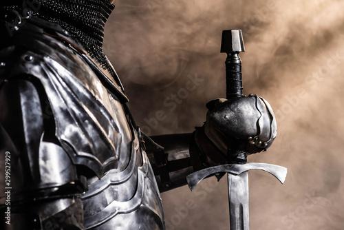 Obraz na płótnie cropped view of knight in armor holding sword on black background