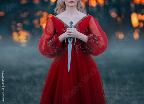 A mysterious blond woman holds a dagger of beautiful Gothic design in her hands Fototapete