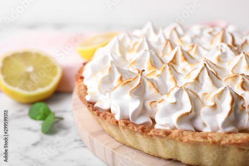 Serving board with delicious lemon meringue pie on white marble table, closeup