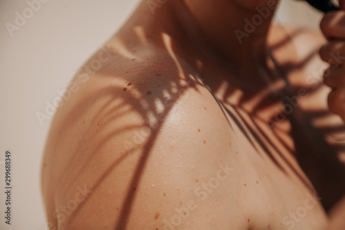 Shadow of palm tree on girl bare shoulder