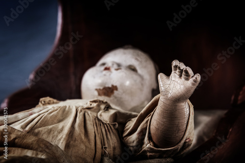 Foto Scary abandoned old baby doll in a cradle