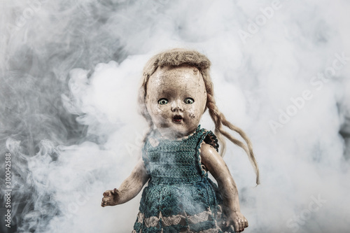 Canvas Print Scary abandoned old baby doll standing in misty smoke