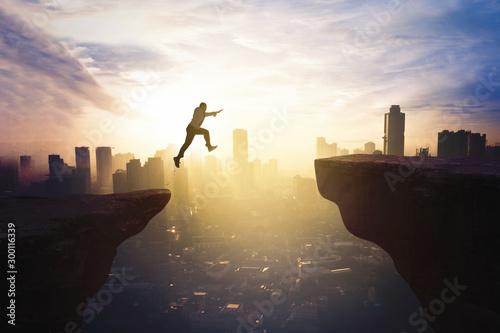 Foto Businessman jumping through gap cliff at sunrise