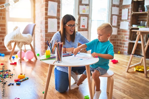 Photo Young caucasian child playing at playschool with teacher