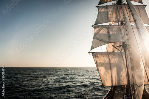 Backlit sails of a traditional tall ship on the atlantic Fotobehang