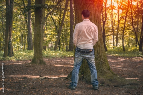 Canvas Print Standing man peeing near big tree in autumn forest
