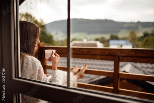Fotografia Young woman on the balcony holding a cup of coffee ore tea in the morning