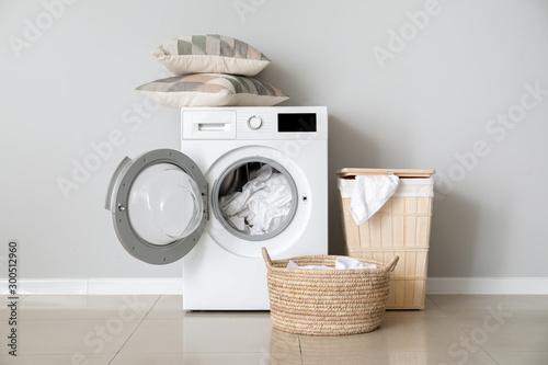 Photo Modern washing machine with laundry near white wall