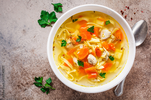 Canvas Print Chicken noodle soup with parsley and vegetables in a white plate, top view