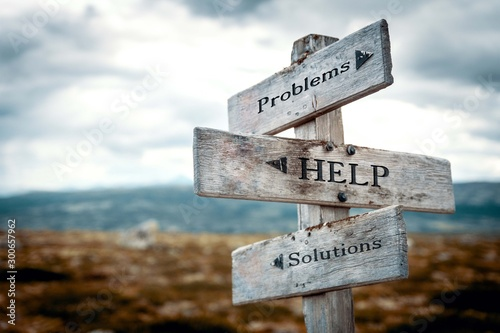 Problems, help, solutions signpost in nature. Rustic, wooden, wilderness, path, help, trouble, solution concept.