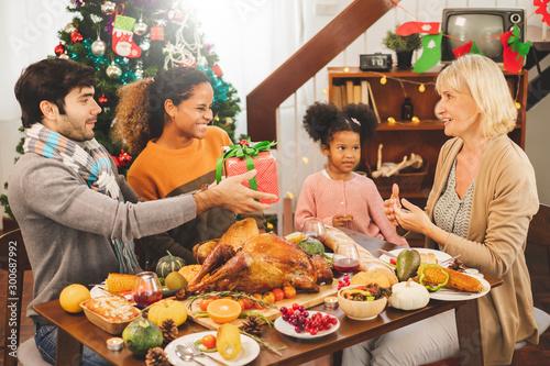 Slika na platnu Thanksgiving family on table, giving present box to grandmother