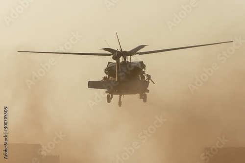 Fotografía Military chopper takes off in combat and war flying into the smoke and chaos and destruction