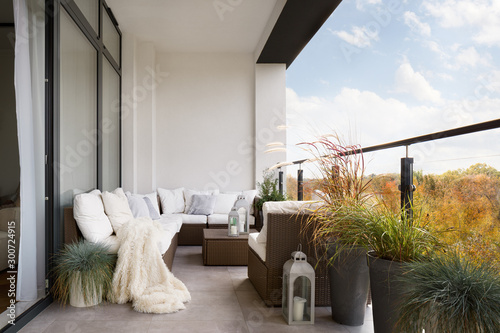 Photo Elegant decorated balcony with rattan outdoor furniture, bright pillows and plan