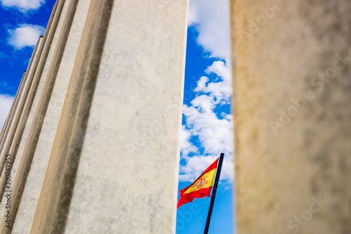Flag of Spain behind a wall at the border to control the passage of illegal immigrants to Europe.
