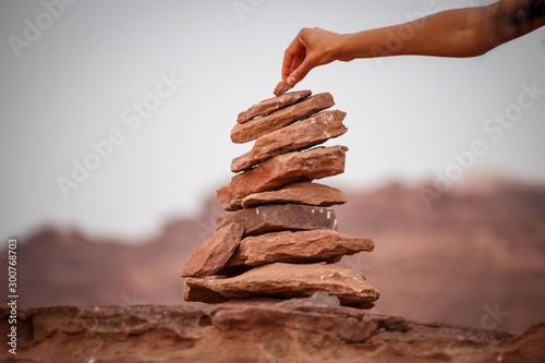 Foto Adding a rock to a stone cairn in the desert of Wadi Ru, Jordan