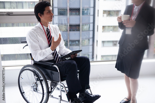 Fotomural 女性社員と談笑する車椅子のビジネスマン