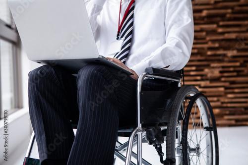 パソコン作業をする車椅子のビジネスマン Fototapet