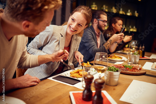 Tableau sur Toile Handsome caucasian ginger taking food out of his girlfriend's plate while sitting in restaurant for dinner