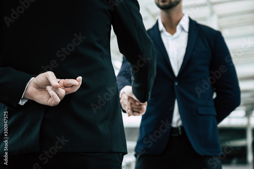 Foto Businessman or politician cross finger, hiding behind his back during he get handshake to another person, businessman