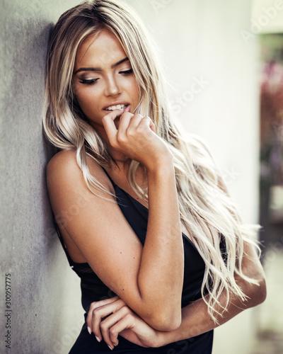 Murais de parede Portrait of beautiful blond young woman in a classic black dress elegant clothes
