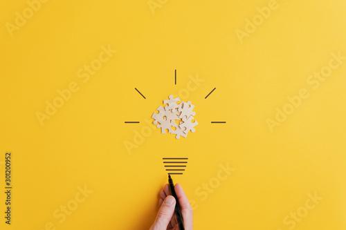 Carta da parati Light bulb over yellow background in vision and idea conceptual image