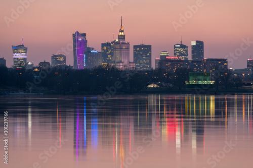 Panorama wieżowców w Warszawie podczas kolorowego zachodu słońca, odbicie w Wiśle, Polska #301239766