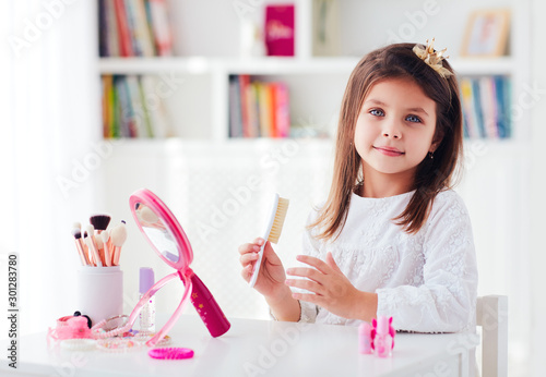 Tableau sur Toile beautiful young girl, kid brushing the hair, applying makeup with toy beauty set