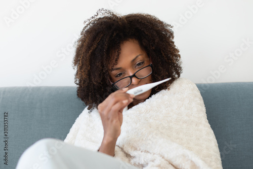 Young woman suffering from a cold or a flu takes her temperature with a thermometer in bed Poster Mural XXL